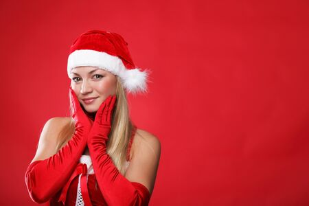Young girl dressed as Santa Claus on a red background photo