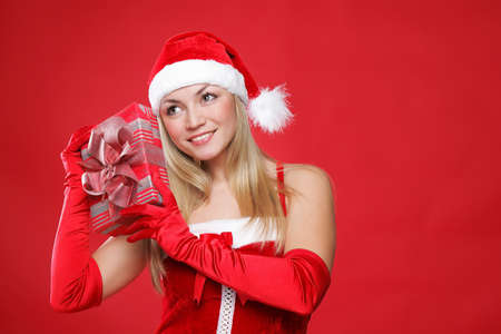 Young beautiful girl dressed as Santa holds a gift in their hands. photo