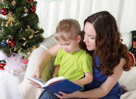 Mum reads to the son the book near a christmas fur-tree photo