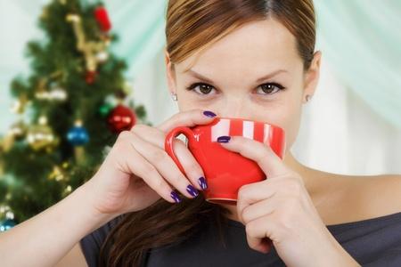 cioccolato natale: La giovane donna bella si siede vicino a un pelliccia-albero di Natale con una tazza rossa