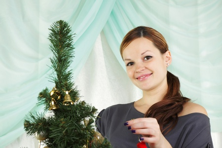 The young beautiful woman decorate a christmas fur-tree  photo