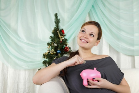 christmas savings: The young beautiful woman sits near a christmas fur-tree and thinks about her savings Stock Photo