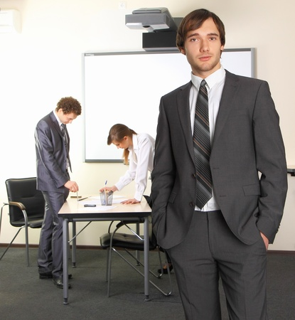 Portrait of business man with team mates discussing in the background Stock Photo - 8496327