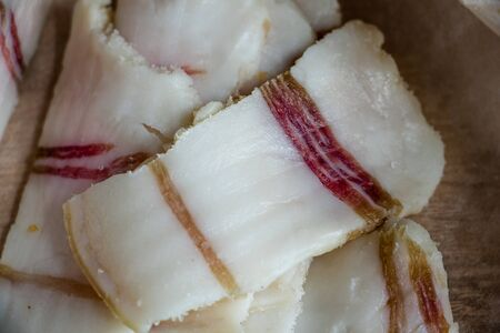 salted pork fat, sliced in beautiful thin slices, national food of Ukrainians, delicious pork fat on a wooden table on parchment