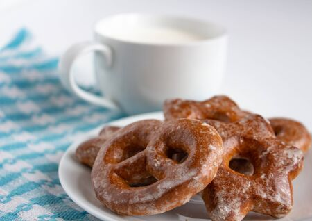 fragrant gingerbread cookies on a white plate with a cup of warm fresh milk, white background, blue napkin, delicious dessert, creating a feeling of homeliness