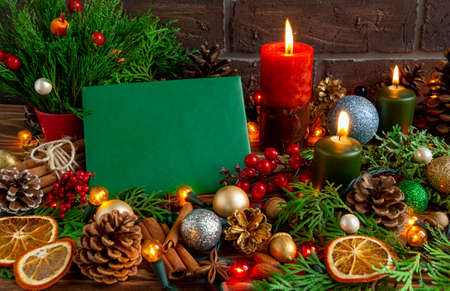 atmospheric Christmas or New Year composition, green blank greeting card, candles, christmas tree, garland. Copy space