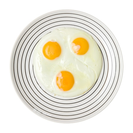 stipe: three fried unbroken eggs on white plate with black stipe, shot from the top