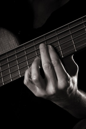 playing six-string electric bass guitar; fretting left hand; toned monochrome image;  photo