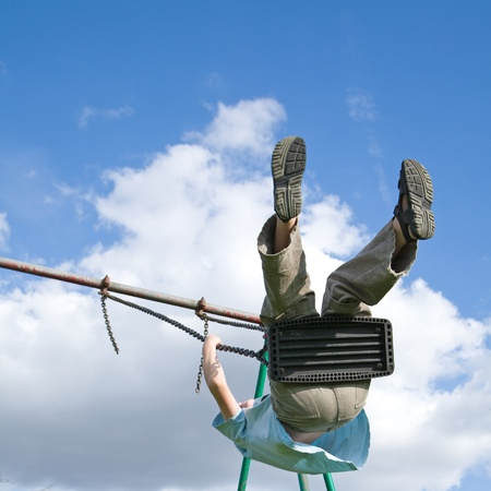 young boy on a swing, flying very high photo