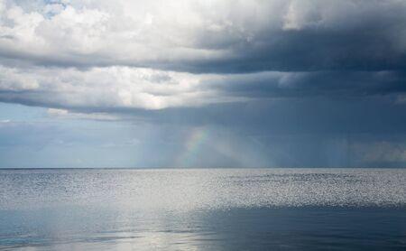 rain clouds and rainbow over northern sea photo