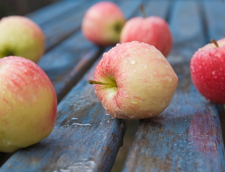wet red apples on a garden table, photo