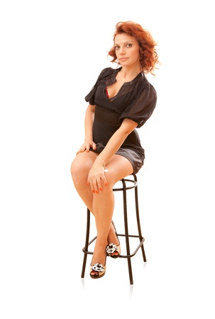 bar stool: pin-up - attracive young slim red-head woman on a bar stool