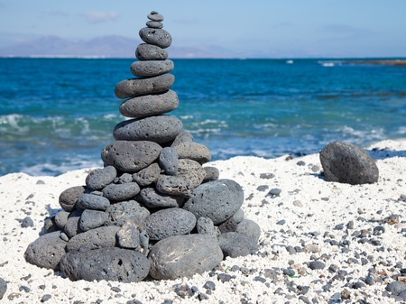 ingenuity: Christmas cairn - cairn built of black volcanic stones  in a shape of Christmas tree on a beach of black and white pebbles on Fuerteventura, Canary Islands, Spain Stock Photo