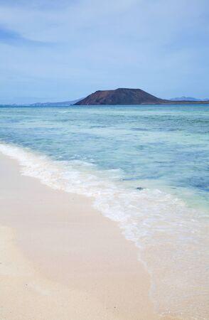 white sand beach on Fuerteventura, small island Isla de Lobos and Lanzarrote in the background photo