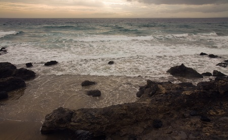 unsettled: Shore of Lanzarote, wintry unsettled sea, outline of Fuerteventura in the distance