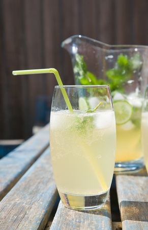 home-made cloudy lemonade with mint and lime; set outside in sunshine Stock Photo