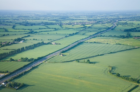 view over the early summer green fields and a dual carriageway road from the air; East Anglia; UK photo