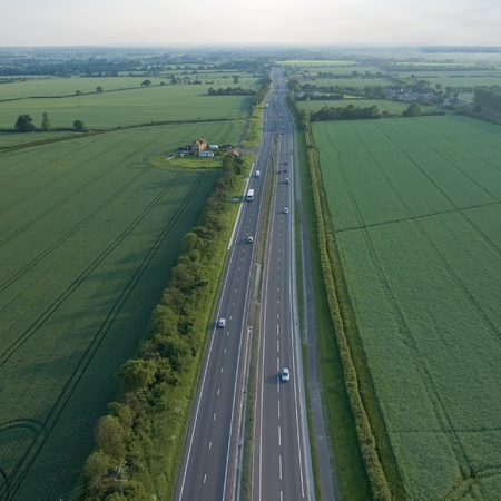 the carriageway: view over the early summer green fields and a dual carriageway road from the air; East Anglia; UK; England