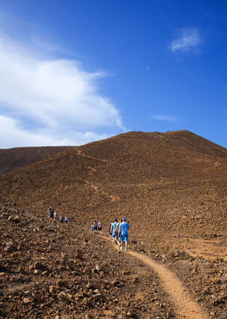 Group of walkers on the path up Bayuyo volcano outside of Corralejo, Fuerteventura, Canary islands, Spain