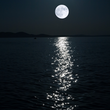 over the moon: full moon over sea Stock Photo