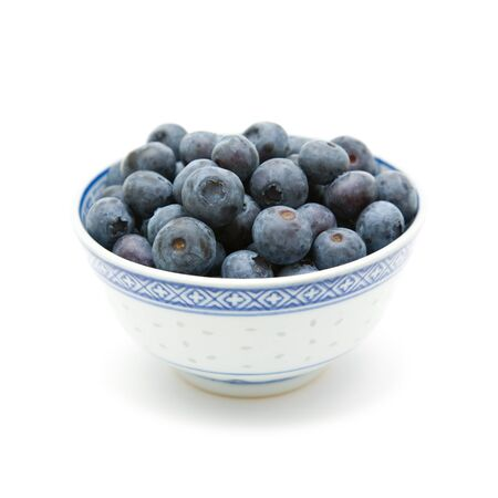 flavoursome: fresh ripe blueberries in a small blue bowl; isolated on white background