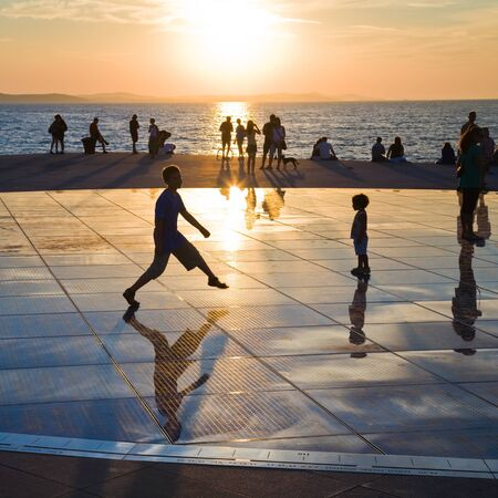 Zadar, Croatia - August 27, 2010: Children play on large circular urban installation Greeting to the Sun