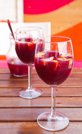 sangria - two glasses and a small pitcher of sangria on a wooden table