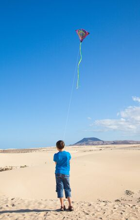 little boy flies a kite in dunes of Corralejo, Fuerteventura photo