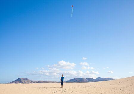 boy flies a kite in dunes of Corralejo, Fuerteventura Stock Photo - 13323151