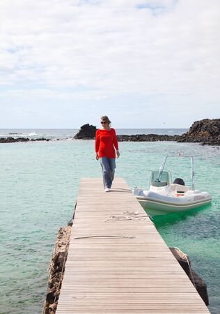 middle-aged woman in casial clothes walks on a wooden pier in a small bay, Isla de LObos, Canary Islands Stock Photo - 13323186