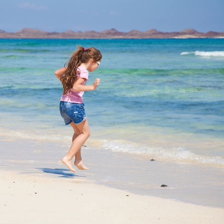 little girl with long brown hair in ponytail in pink t-shirt and denim shorts by the ocean photo