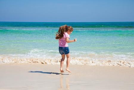 바다로 분홍색 t-셔츠와 데님 반바지에 포니 테일, 긴 갈색 머리를 가진 어린 소녀