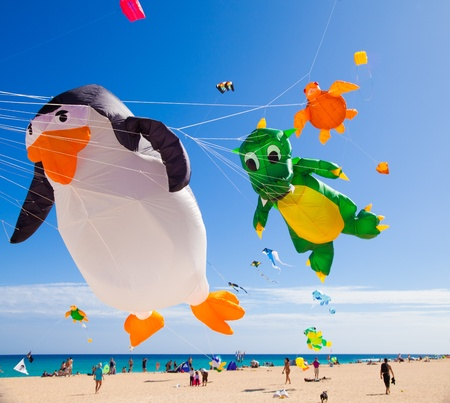 FUERTEVENTURA - NOVEMBER 13: Viewers watch from the ground as multicolored kites fill the sky at 24th International Kite Festival (Festival de Cometas), November 13, 2011 in Dunes of Corralejo, Fuerteventura, Spain Stock Photo - 13365298
