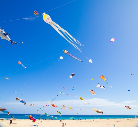 FUERTEVENTURA - NOVEMBER 13: Viewers watch from the ground as multicolored kites fill the sky at 24th International Kite Festival (Festival de Cometas), November 13, 2011 in Dunes of Corralejo, Fuerteventura, Spain