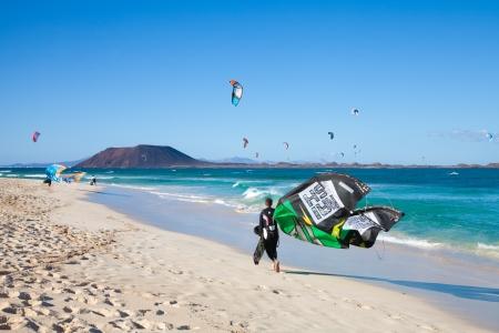 CORRALEJO, SPAIN - APRIL 28: Kitesurfers take to water en masse as wind and waves combination turns perfect on 28 April 2012 in Corralejo, Fuerteventura, Spain