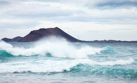 swell: sea swell by the northern shore of Fuerteventura, small volcanic island Isla de Lobos in the background Stock Photo