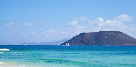 Northern Fuerteventura, view towards Isla de Lobos, small white yacht in front of it photo