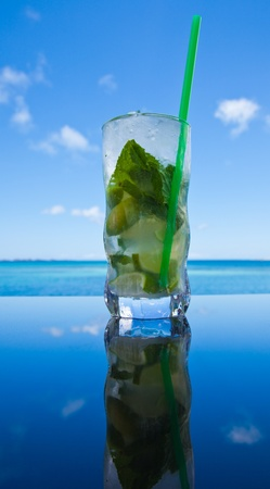 cocaine: Mojito by the ocean - cocktail in a tall glass on a reflective table top, sea in the background