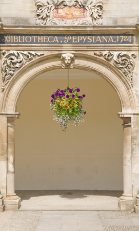 house coat: Central arch in the collonade of Library Building of Magdelene College, Cambridge University, UK, elegant, old, house, coat of armd, sign, hanging basket, flowers,