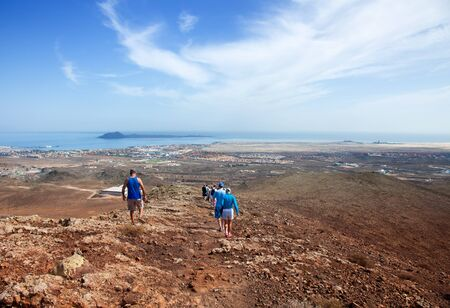 volcano slope: group of walkers walking down the slope of  Bayuyo volcano next to Corralejo, Fuerteventura, Canary Islands