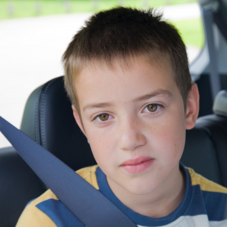 boy long hair: boring car journey - cute little boy in a back seat of a car Stock Photo