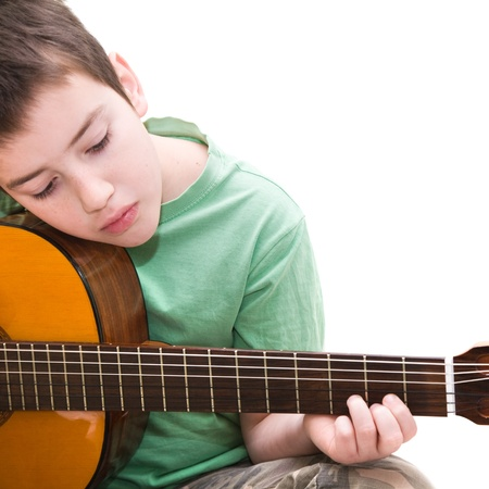 nine years old: caucasian boy practicing; playing acoustic guitar;isolated on white background; Stock Photo