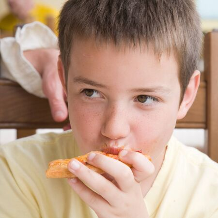 my piece of pizza - cute little caucasian boy eating pizza, face somewhat dirty with tomato sauce photo