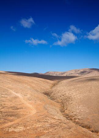 eau de pluie: rouge paysage volcanique de l'int�rieur de Fuerteventura, �les Canaries, dirt track et des eaux pluviales vall�e, barranco, formant un r�sum�