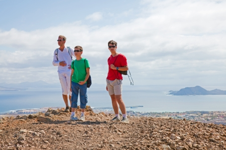 hike up Bayuyo - father and two sons on the Bayuyp volcano; Isla de lobos and Corralejo in the backgroun photo