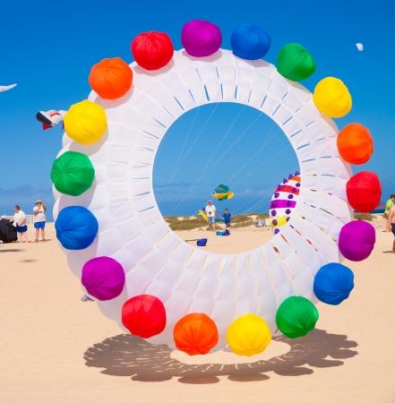 FUERTEVENTURA - NOVEMBER 13: Viewers watch from the ground as multicolored kites fill the sky at 24th International Kite Festival (Festival de Cometas), November 13, 2011 in Dunes of Corralejo, Fuerteventura, Spain