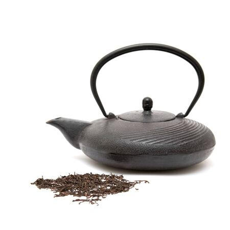 tetsubin: cast iron eastern black teapot and scattered dry tea leaves on white background