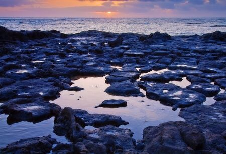 Low tide on the edge of El Cotillo, Fuerteventura, basalt sea floor revealed photo