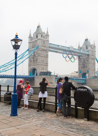 London 2012 - tourists photographing tower bridge with olympic symbol