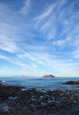predominantly: Fuerteventura, view towards Isla de Lobos and Lanzarote, natural background of predominantly sky Stock Photo